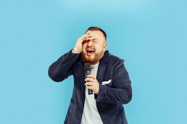 Молодой человек с микрофоном на синей стене