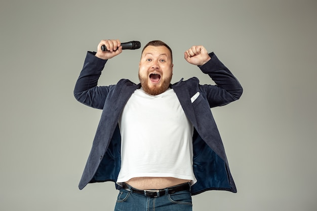 Молодой человек с микрофоном на серой стене, ведущий с микрофоном