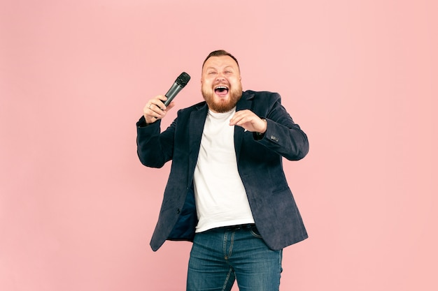 Young man with microphone on pink background, leading with microphone