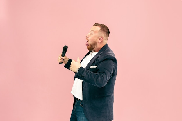 Young man with microphone on pink, leading with microphone