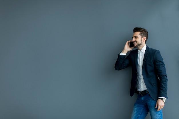 Молодой человек с мобильным телефоном в офисе