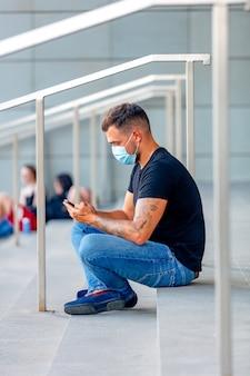Молодой человек с мобильным телефоном на ступеньках университетского городка