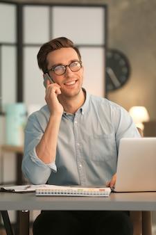밤에 사무실에서 일하는 휴대 전화와 함께 젊은 남자
