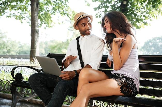 公園のベンチに座っているモデルと若い男
