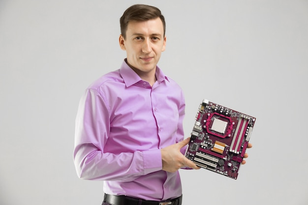 Young man with motherboard in his hands is isolated on light