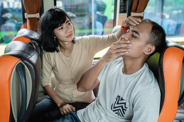A young man with motion sickness and a woman holding his forehead while sitting on a bus bench while traveling
