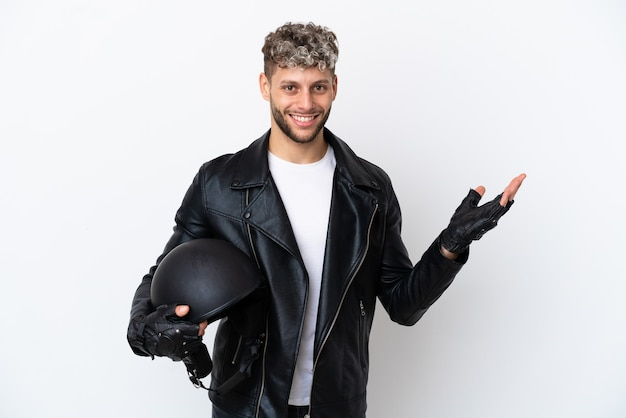 Young man with a motorcycle helmet isolated on white background extending hands to the side for inviting to come