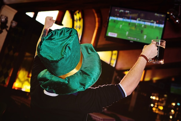 A young man with a mug of dark beer and a green hat from oktoberfest watching football in a sports bar or pub.