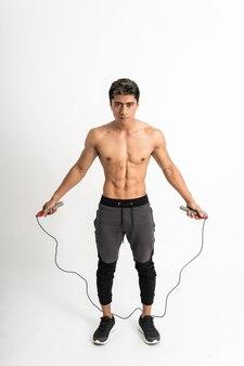 前方を向いた2つのハンドスタンドで縄跳びの縄を保持している筋肉ボディを持つ若者