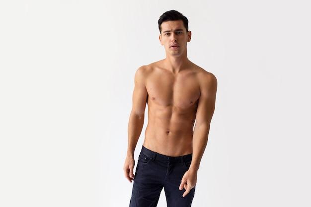 Молодой человек с голым торсом в черных джинсах позирует на белом