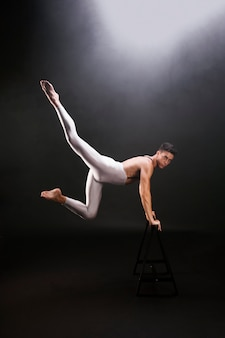 Young man with naked torso jumping and leaning on wooden stand while looking at camera