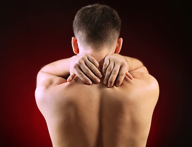 Young man with neck pain, on red surface