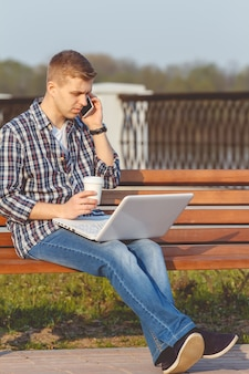 Young man with the notebook. the concept of remote working outdoors