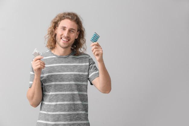 Молодой человек с лекарствами для оральной эректильной дисфункции и презервативом на серой поверхности