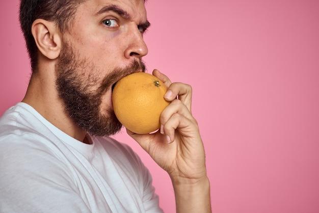 白いtシャツのピンクの背景にオレンジ色の若い男は、モデルの手でジェスチャーを楽しんでいます。高品質の写真