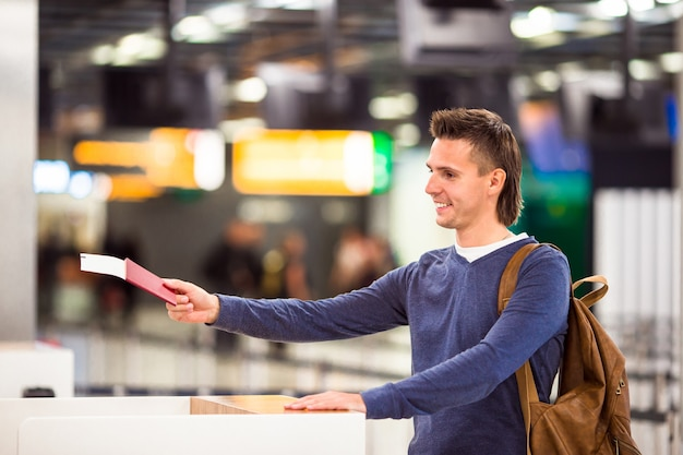 Young man with passports and boarding tickets at the front desk in airport