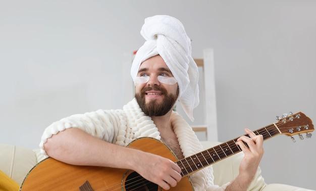 눈 아래 패치가 있는 젊은 남자는 집에서 기타를 연주합니다. 남성과 음악가를 위한 미용의 개념입니다. 집에서 즐기는 스파, 음악, 스킨케어