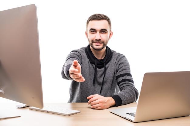 Молодой человек с компьютером и ноутбуком, приветствуя вас за своим столом, изолированным на белом