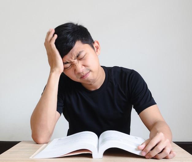 펜을 들고 있는 청년은 책상 위에 있는 책으로 머리를 만지고 문제로 긴장을 느낀다