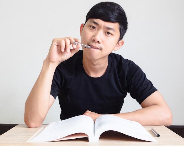 펜을 든 청년은 책상 위에 책을 놓고 진지한 얼굴로 카메라를 보고 있다.