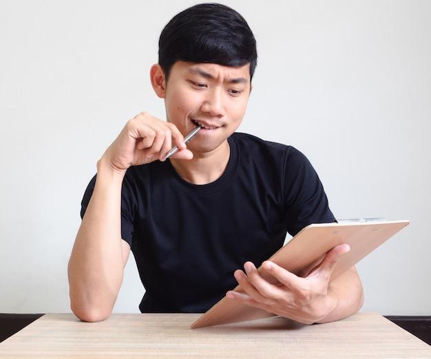 펜을 든 청년은 책상 위에 책을 놓고 생각하고 진지한 얼굴을 하고 있다.