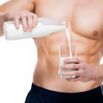 Young man with perfect body pouring milk into a glass - isolated on white wall.