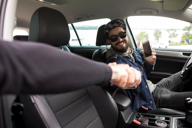 Young man with phone greeting friend while sitting in car