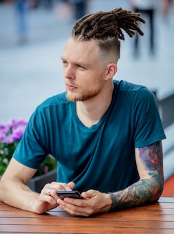 Young man with phone is sitting at table in a cafe in the city
