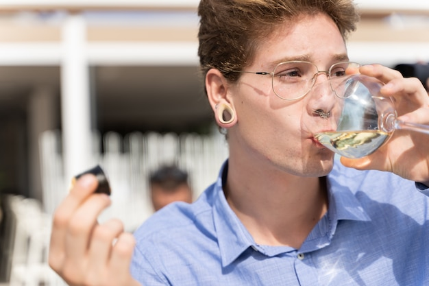 Young man with piercings and lasses drinking white wine while is holding a piece of sushi in the other hand
