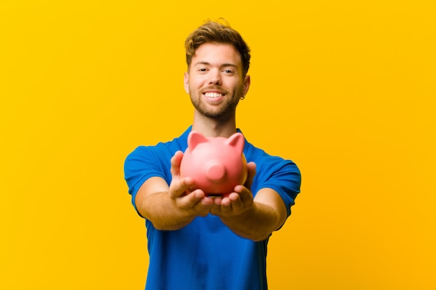 Young man with a piggy bank against orange background