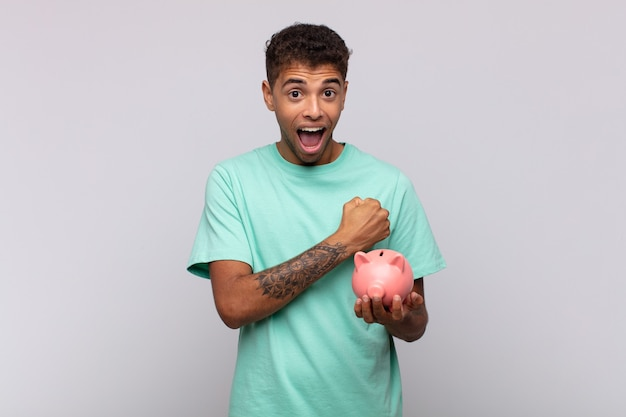 Young man with a piggy bank feeling happy, positive and successful, motivated when facing a challenge or celebrating good results