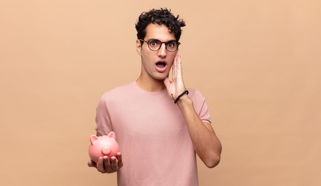Young man with a piggy bank feeling shocked and scared, looking terrified with open mouth and hands on cheeks