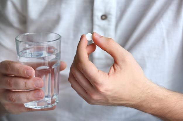 알 약과 물, 근접 촬영 유리 젊은 남자