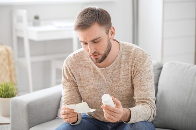 Молодой человек с таблетками и инструктаж дома