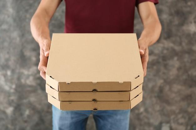 ピザの箱を持つ若い男。フードデリバリーサービス