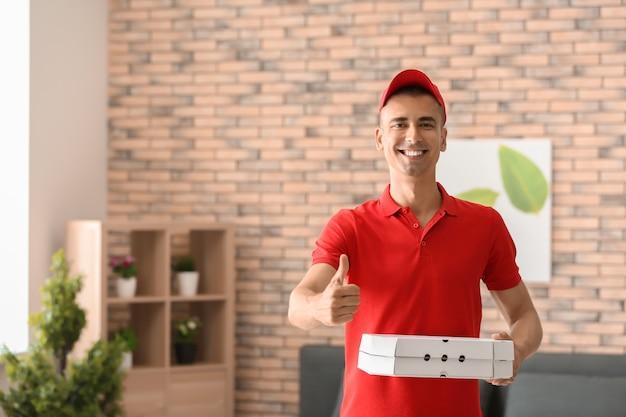 실내에 엄지 위로 제스처를 보여주는 피자 상자와 젊은 남자. 음식 배달 서비스