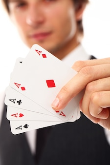 Young man with poker cards, close up