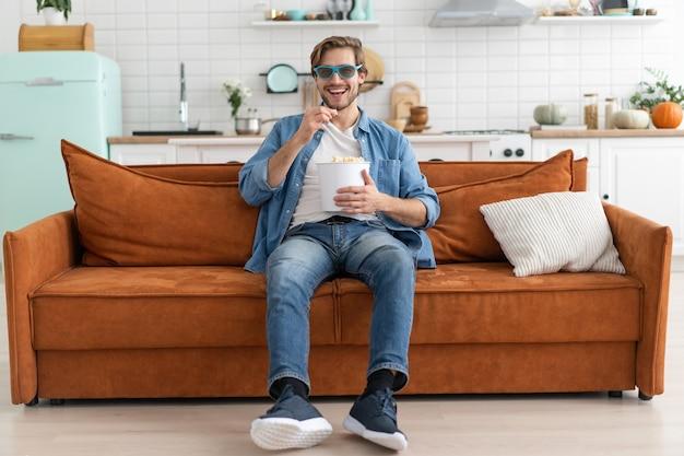 Молодой человек с попкорном в руках смотрит телевизор дома.