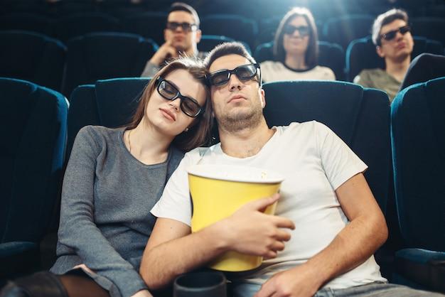Молодой человек с попкорном спит в кино