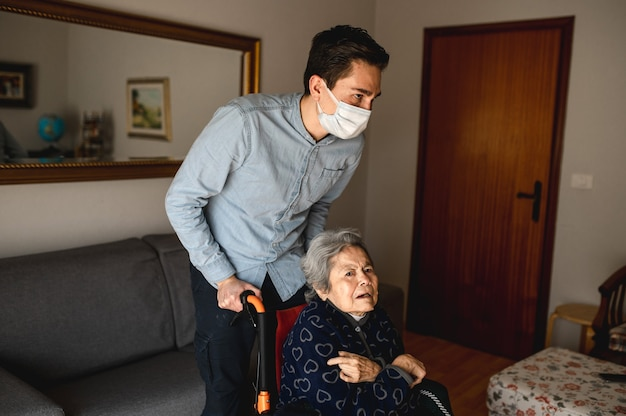 Young man with protective face mask pushing wheelchair with old sick aged woman. family, home care concept.