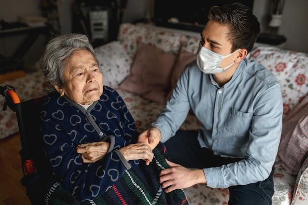 Молодой человек с защитной маской сидит рядом с больной пожилой женщиной в инвалидной коляске. семья, концепция домашнего ухода.