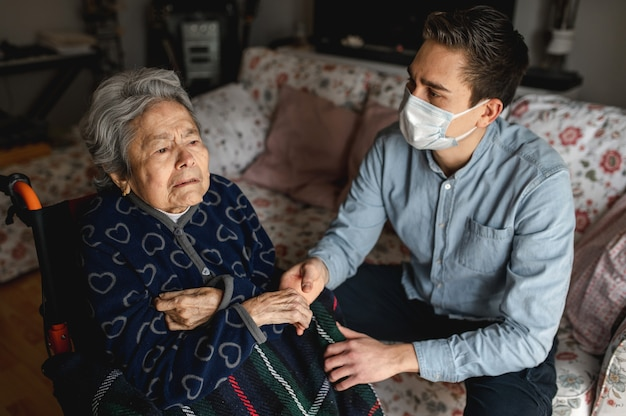 Young man with protective face mask sitting next to an old sick aged woman in wheelchair. family, home care concept.