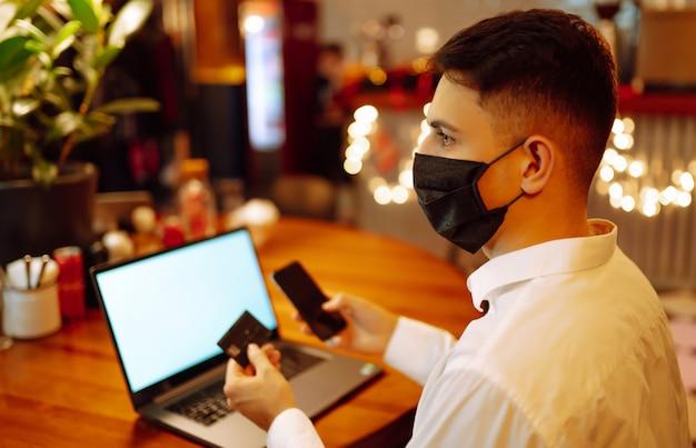 Молодой человек с защитной маской работает на ноутбуке дома во время зимних каникул.