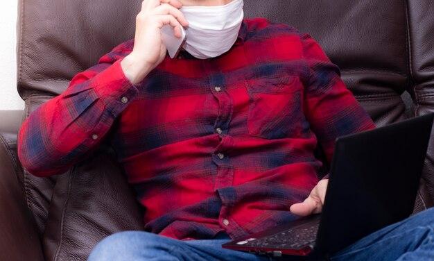 保護のために室内でスマートフォンと相互作用する防護マスクを持つ若者。 covid-19の自己絶縁