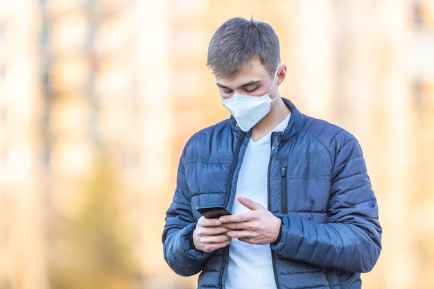 顔に保護マスクをつけた青年が携帯電話から通信します。コロナウイルスcovid-19の概念。