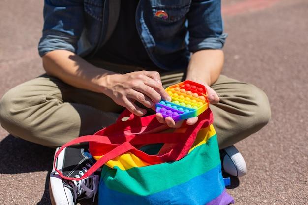 レインボーポップの若い男は、プライド月の間に抗ストレス感覚のおもちゃとlgbtqの再利用可能な綿のバッグをいじくり回します。自由、多様性、受容、lgbtの概念