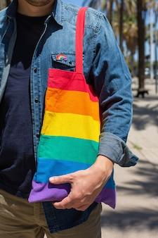 プライド月の間に虹の再利用可能なバッグとlgbtqバッジを持つ若い男。自由、多様性、受容、lgbtの概念