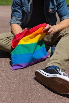 虹の再利用可能なバッグとlgbtqバッジを持つ若い男は、プライド月の間に舗装に座っています。自由、多様性、受容、lgbtの概念