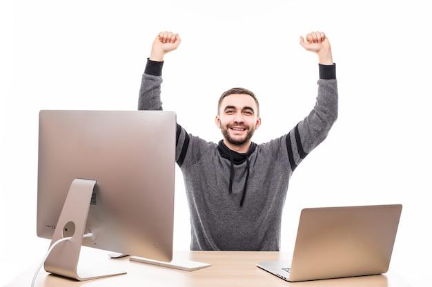 Молодой человек с поднятыми кулаками, используя ноутбук и персональный компьютер за изолированным столом на белом