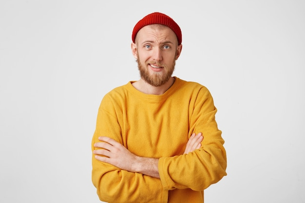 Young man with a red beard,wearing hat and a yellow sweater, stands with folded arms, looks skeptical